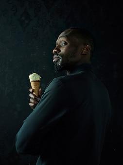 Portret van trieste afro-amerikaanse man met ijs op zwarte studio achtergrond