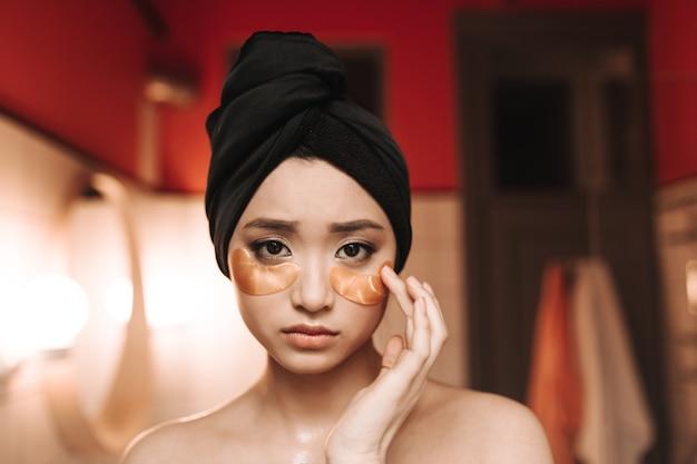 Portret van trieste aziatische vrouw in handdoek en met gouden vlekken onder ogen