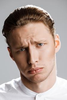 Portret van trieste blanke man over witte muur