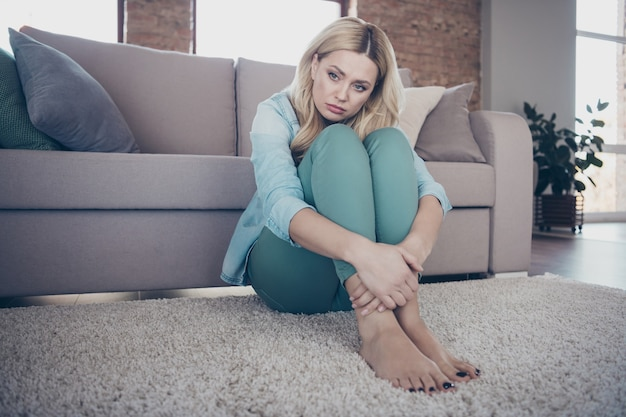 Portret van trieste depressieve golvende dame zittend op tapijt denken