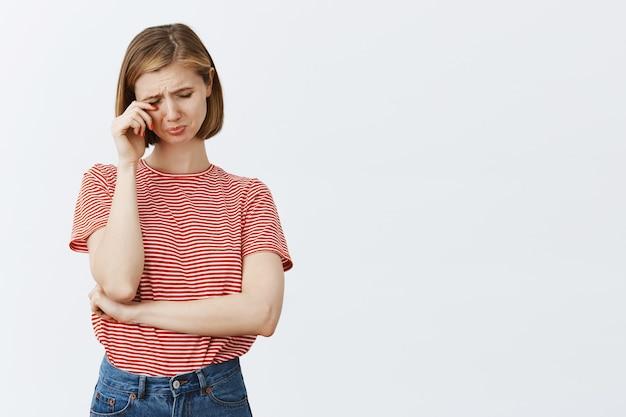 Portret van trieste en rouwende jonge vrouw die snikt, huilt en tranen afveegt