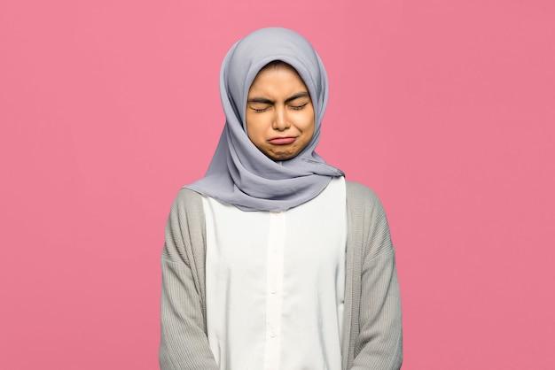 Portret van trieste jonge aziatische vrouw sloot haar ogen over geïsoleerde roze achtergrond