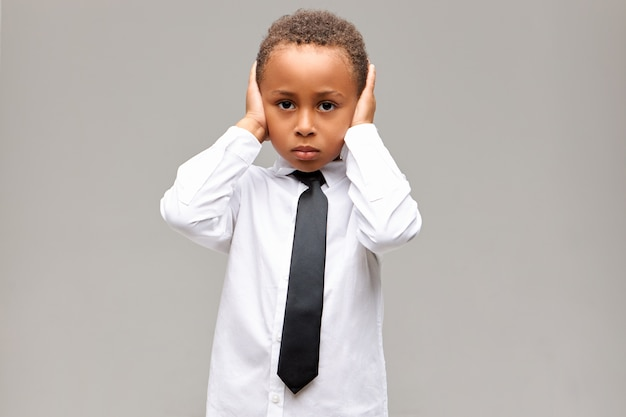 Portret van trieste ongelukkige afro-amerikaanse jongen in schooluniform die depressieve gelaatsuitdrukking van streek hebben, oren bedekt met handen, kan niet tegen ouders vechten. lichaamstaal, reactie en gevoelens