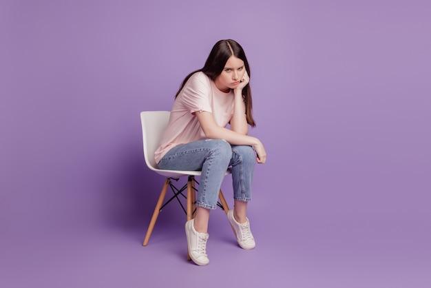 Portret van trieste ongelukkige gefrustreerde wanhopige stemming zit stoel vrouw geïsoleerd op paarse achtergrond