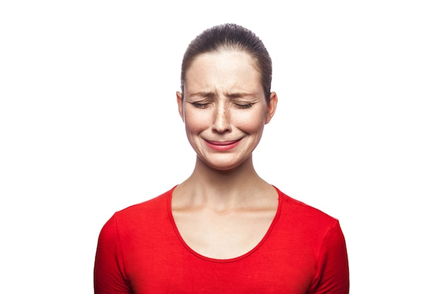 Portret van trieste ongelukkige huilende vrouw in rode t-shirt met sproeten