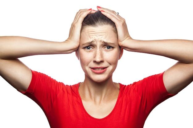 Portret van trieste ongelukkige vrouw in rode t-shirt met sproeten