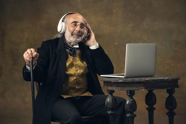 Portret van trieste oudere grijsharige man heer aristocraat of acteur geïsoleerd op donkere muur