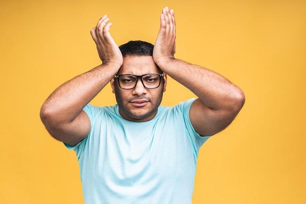 Portret van trieste updet of verveelde afro-amerikaanse zwarte indiase jongeman die staat en naar de camera kijkt met een ontevreden verdrietig gezicht. indoor studio opname, geïsoleerd op gele achtergrond.