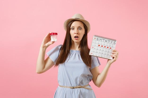 Portret van trieste vrouw in blauwe jurk met witte fles met pillen, vrouwelijke periodenkalender, menstruatiedagen controleren geïsoleerd op de achtergrond. medische gezondheidszorg, gynaecologisch concept. ruimte kopiëren.
