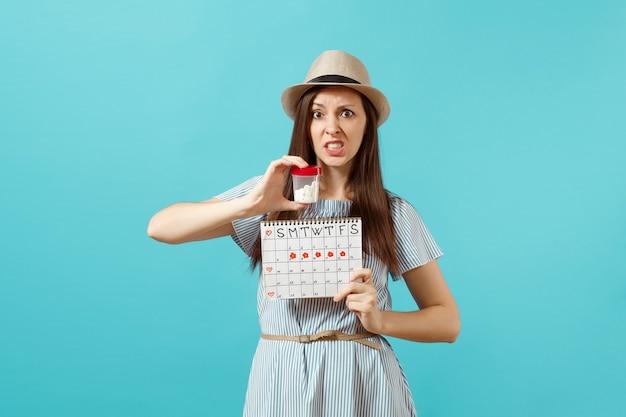 Portret van trieste vrouw in jurk met witte fles met pillen, vrouwelijke menstruatiekalender, menstruatiedagen controleren geïsoleerd op blauwe achtergrond. medische gezondheidszorg, gynaecologisch concept. ruimte kopiëren.