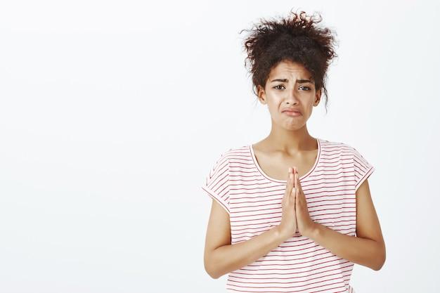 Portret van trieste vrouw met afro kapsel poseren in de studio