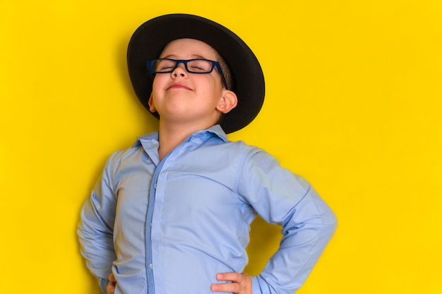 Portret van trotse mooie kleine die jongen in hoed en overhemd op geel wordt geïsoleerd