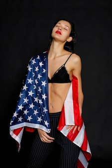 Portret van trotse vrouwelijke atleet verpakt in amerikaanse vlag tegen zwarte achtergrond. gespierde jonge vrouw die vol vertrouwen naar de camera kijkt.