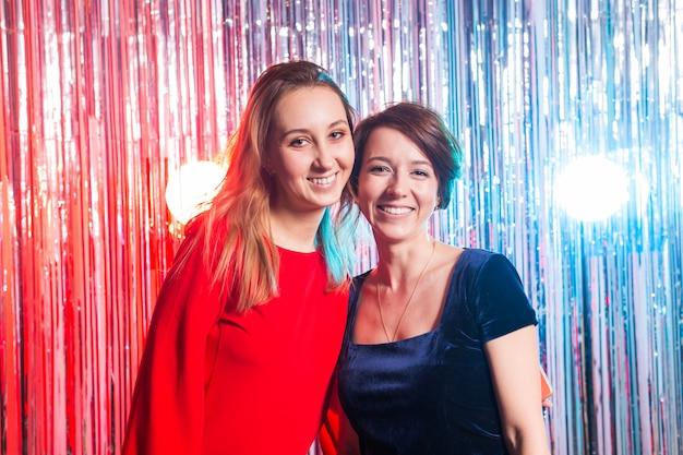 Portret van twee aantrekkelijke gelukkige vrouwen in avondjurken die en camera koesteren bekijken die over zilverkleurige glanzende achtergrond wordt geïsoleerd. verjaardagsfeestje, vakantie en nachtclub concept.