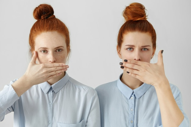 Portret van twee aantrekkelijke roodharigevrouwen in identieke overhemden die lippen met handen bedekken