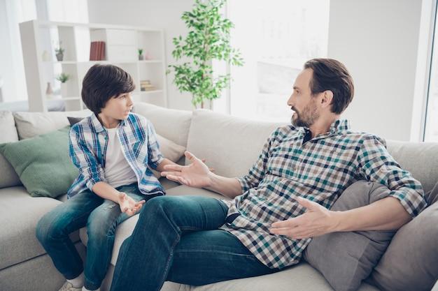Portret van twee aardige vriendelijke jongens vader en pre-tiener zoon zittend op de bank bespreken psychologie generatie problemen in lichte witte moderne stijl interieur woonkamer
