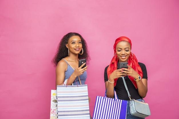 Portret van twee afrikaanse vrouwen die boodschappentassen vasthouden terwijl ze hun smartphones gebruiken