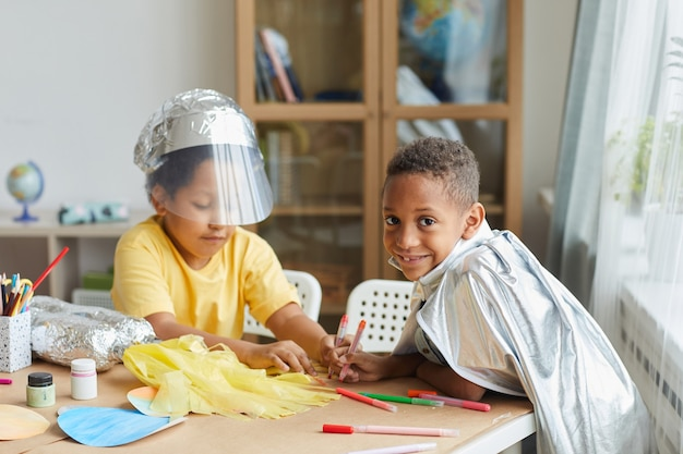 Portret van twee afro-amerikaanse jongens die ruimtepakken maken terwijl ze genieten van kunst- en ambachtles in de kleuterschool of het ontwikkelingscentrum