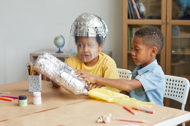Portret van twee afro-amerikaanse jongens die ruimtepakken maken van folie terwijl ze genieten van kunst- en knutsellessen in de kleuterschool of het ontwikkelingscentrum