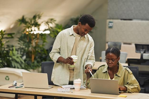 Portret van twee afro-amerikaanse mensen werken in moderne open ruimte kantoor, focus op jonge man collega instrueren en wijzend op laptop scherm, kopie ruimte