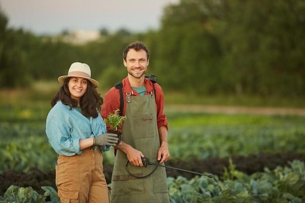 Portret van twee arbeiders in veld bij groenteplantage, jonge vrouw en man die bij camera op voorgrond glimlachen, exemplaarruimte
