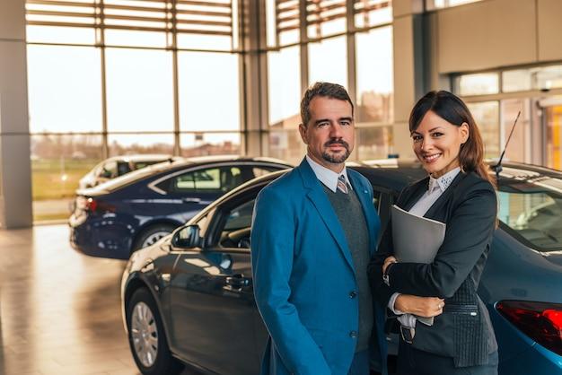 Portret van twee autohandelaren in salon.