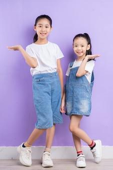 Portret van twee aziatische meisjes op paarse achtergrond
