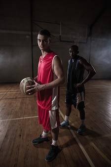 Portret van twee basketbalspelers het stellen