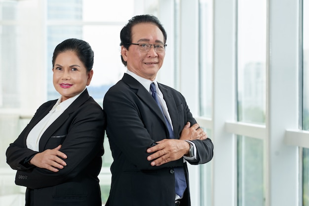 Portret van twee bedrijfsmensen die zich rijtjes bij het bureauvenster bevinden