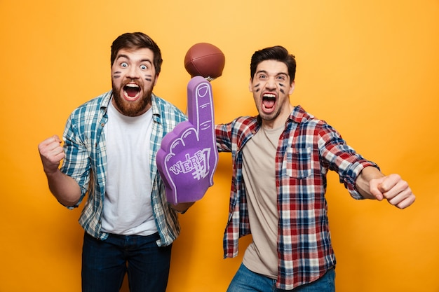 Portret van twee blije jonge mannen die rugbybal houden