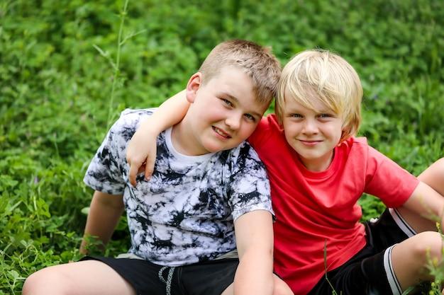 Portret van twee blonde broers die glimlachen terwijl ze elkaar knuffelen
