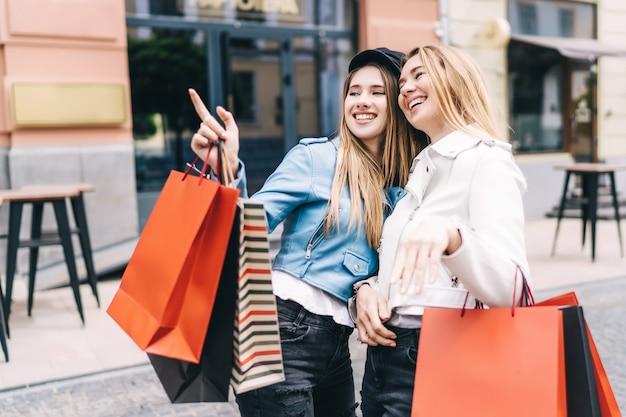 Portret van twee blondines midden op straat winkelend, een van hen wijst naar de discountwinkels