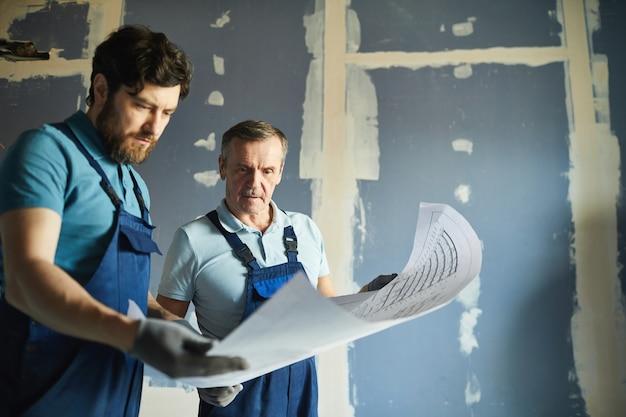 Portret van twee bouwvakkers die plannen houden en tegen de droge muur staan tijdens het renoveren van huis, kopie ruimte