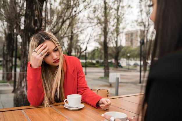 Portret van twee boze vrienden die een serieus gesprek hebben en bespreken terwijl ze in coffeeshop zitten
