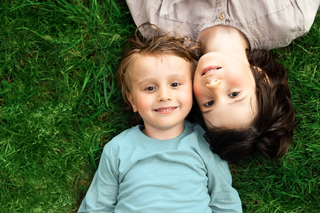 Portret van twee broers die op een gras in een park liggen. glimlachende gelukkige kinderen buitenshuis. broers en zussen vriendschap.