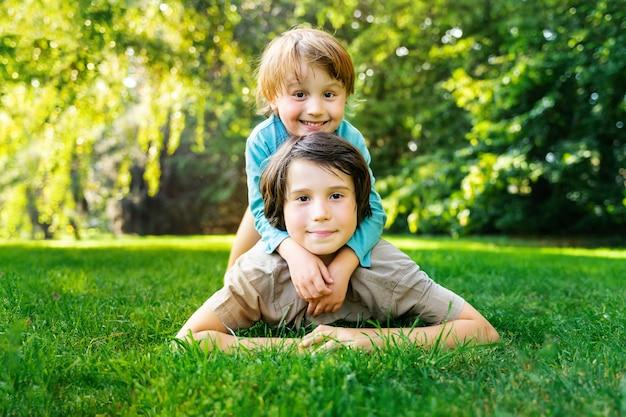 Portret van twee broers die op een gras liggen en samen spelen in een park bij de zonsondergang. glimlachende gelukkige kinderen buitenshuis. broers en zussen vriendschap.