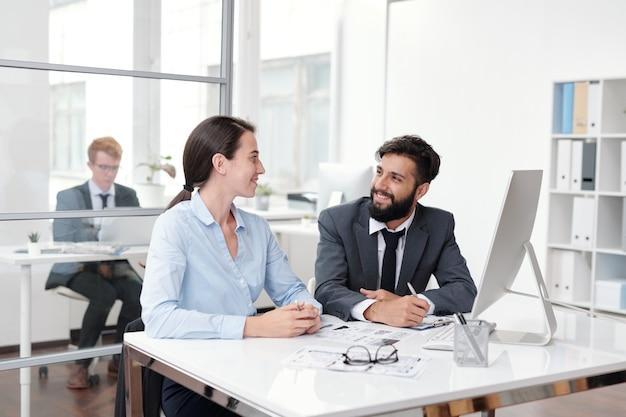 Portret van twee collega's kijken elkaar aan en lachend zittend aan een bureau in kantoor, kopieer ruimte