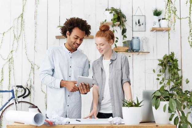 Portret van twee creatieve arbeiders die blauwdrukken samen maken