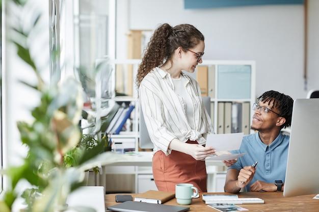 Portret van twee creatieve jonge mensen die foto's bekijken terwijl ze bezig zijn met bewerken en publiceren in een moderne kantoor-, kopieerruimte