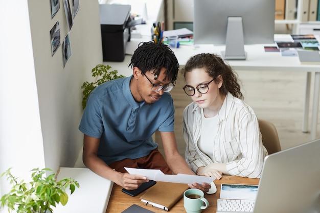 Portret van twee creatieve jonge mensen die foto's bekijken terwijl ze werken aan het bewerken en publiceren in een moderne kantoor-, kopieerruimte