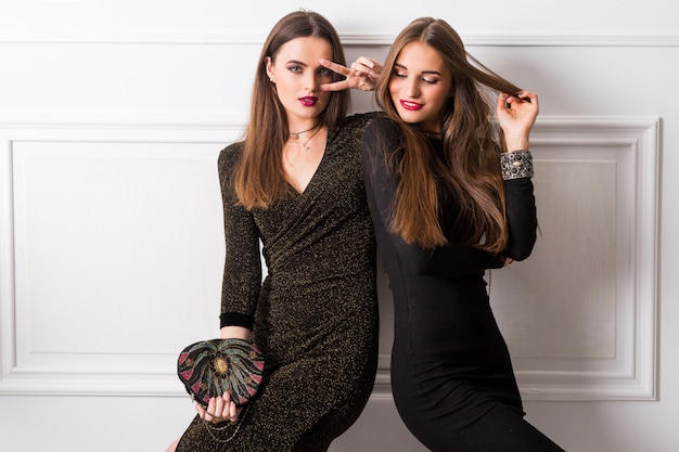 Portret van twee elegante jonge vrouwen in glamour lange jurken die zich voordeed op een witte muur