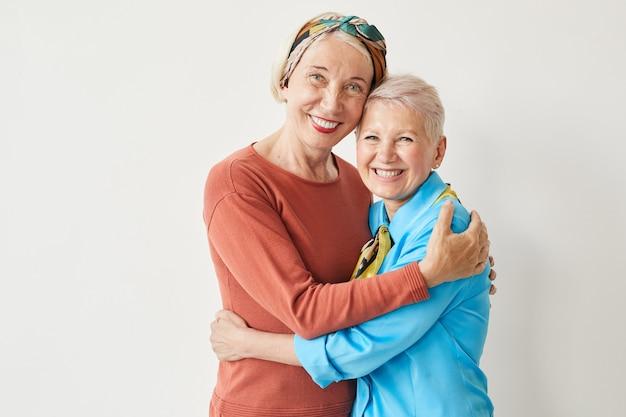 Portret van twee elegante rijpe vrouwen die elkaar omhelzen en bij camera glimlachen tegen de witte achtergrond