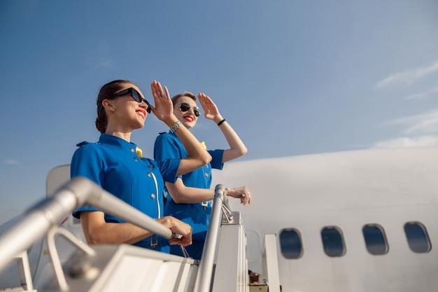 Portret van twee elegante stewardessen in blauw uniform en zonnebril die de ogen met de hand bedekken en ver weg kijken, samen op de airstair staan. vliegtuigbemanning, bezettingsconcept