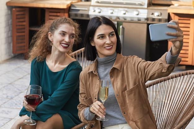 Portret van twee elegante vrouwen selfie foto nemen en glimlachend in de camera terwijl u geniet van buitenfeest op terras,
