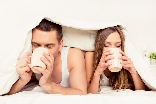 Portret van twee geliefden die thee drinken onder deken close-up