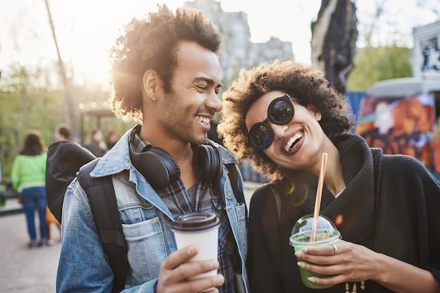 Portret van twee geliefden met afro-kapsels, wandelen in het park en koffie drinken terwijl ze praten en genieten van tijd doorbrengen op food festival.