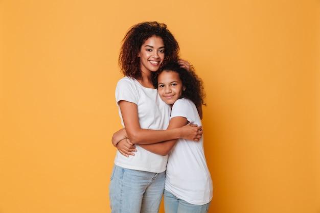 Portret van twee gelukkige afrikaanse zusters knuffelen
