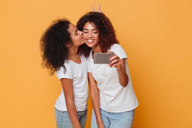 Portret van twee gelukkige afro-amerikaanse zusters die selfie met smartphone, leuke kus nemen
