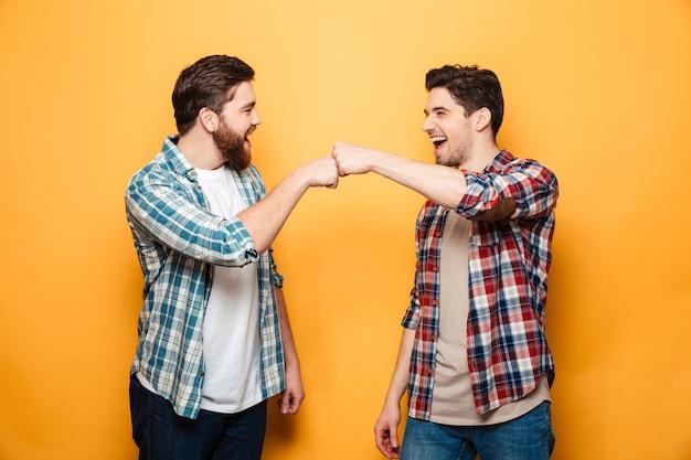 Portret van twee gelukkige jonge mannen die vuistbuil geven