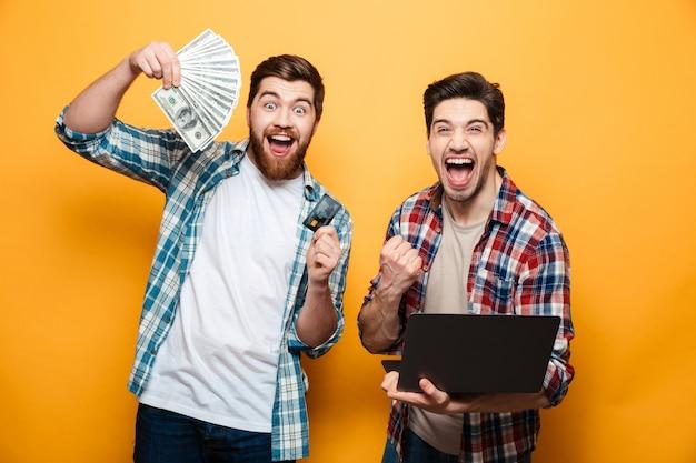 Portret van twee gelukkige jonge mensen die laptop houden